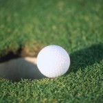 Golf ball traveling towards cup